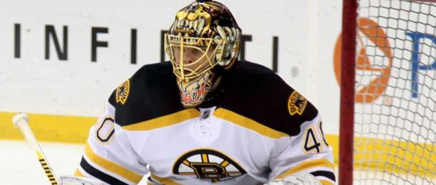 The Boston Bruins goalie stands ready to defend the goal.