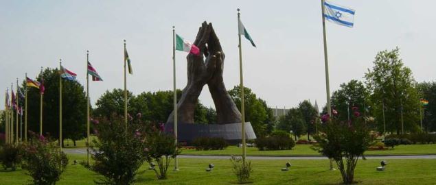 Avenue of Flags and bronze sculpture Praying Hands and at the entrance to Oral Roberts.