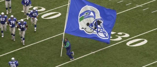 The Seattle Seahawks flag runner runs across the field before a game.