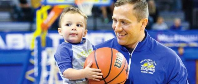 South Dakota State's Coach Otzelberger holding his son Jayce on a basketball court.