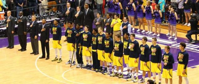 The Michigan Wolverines men's basketball team standing for the National Anthem.